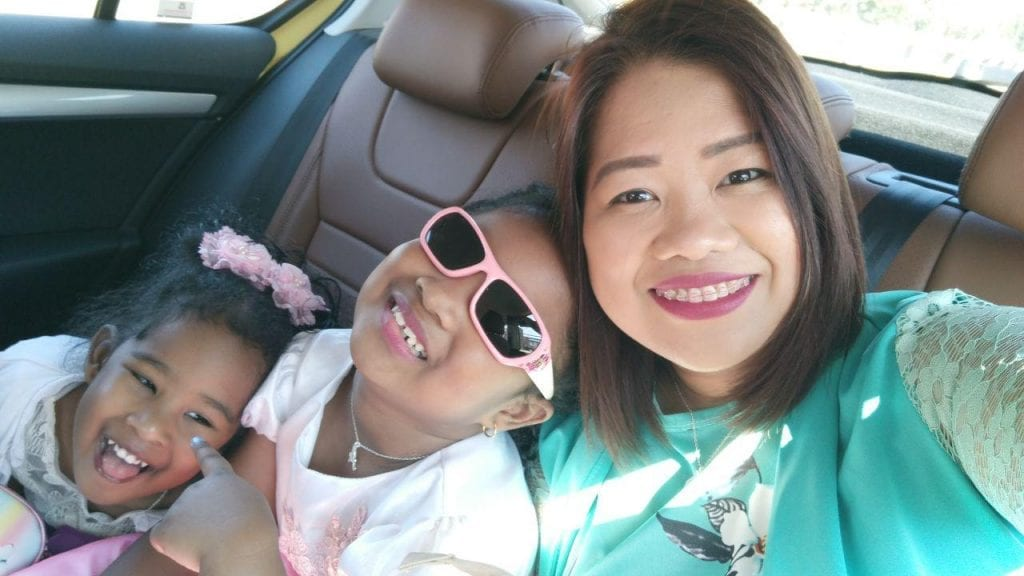A mom and two daughters in a car smiling.