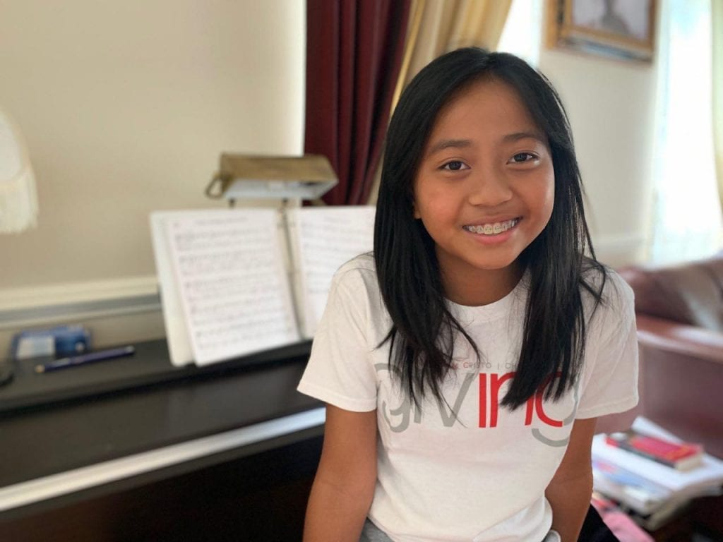 Girl with INC Giving Tshirt with Piano in Background.