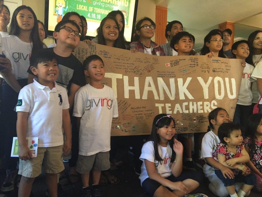 Young INC Giving Volunteers with a thank you sign for teacher appreciation day.