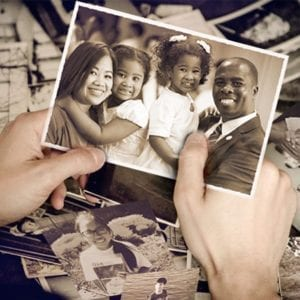 hands holding a picture of a family of four, with more pictures underneath hands on the table