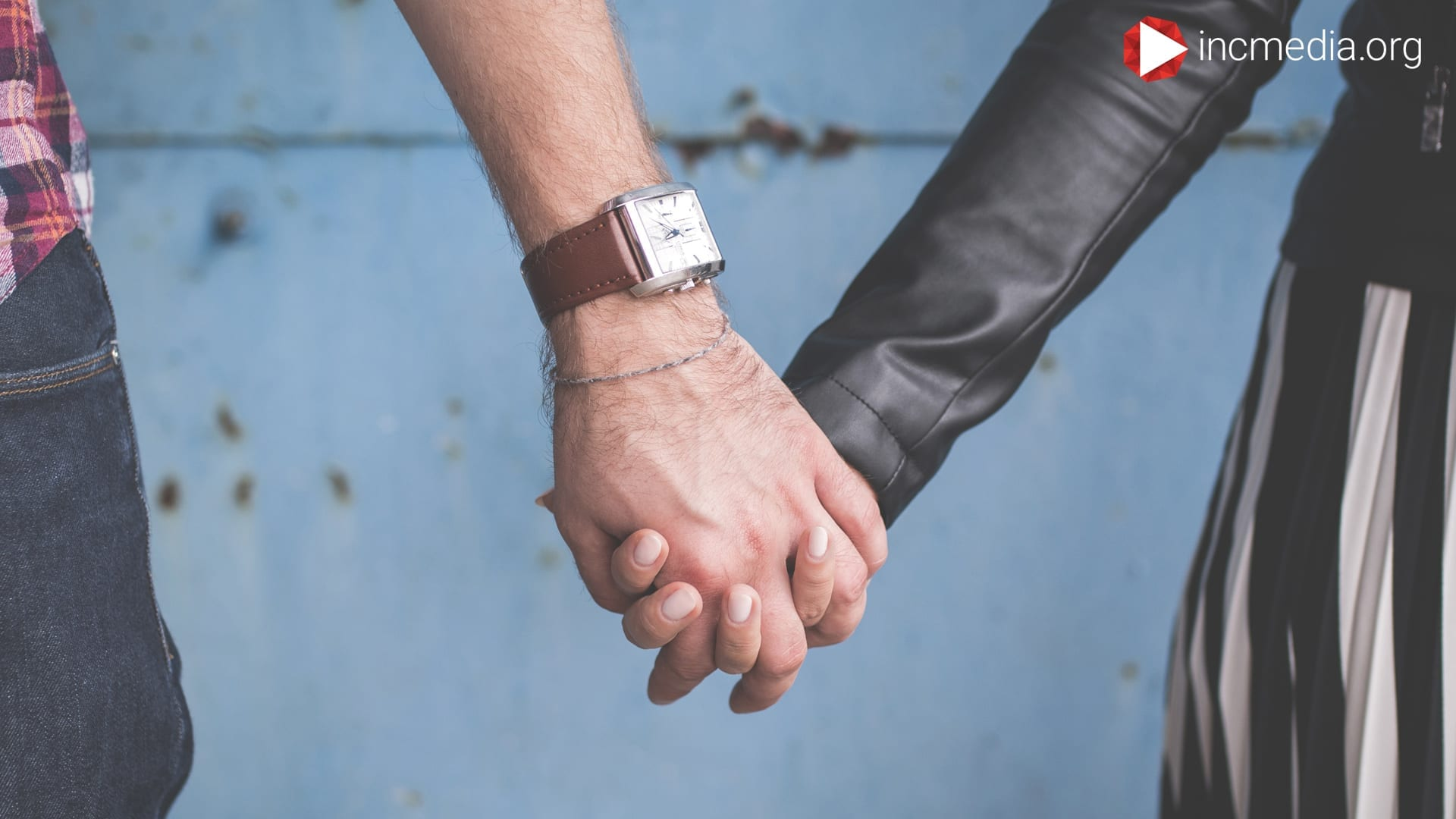 man with watch and bracelet and woman wearing black leather jacket, holding hands
