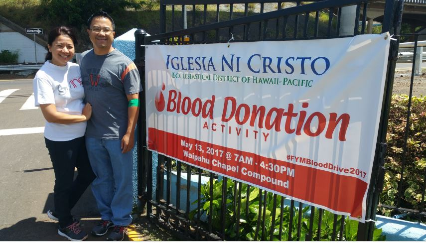 A couple smiling together outdoors in front of an iron gate and banner that reads Blood Donation Activity.