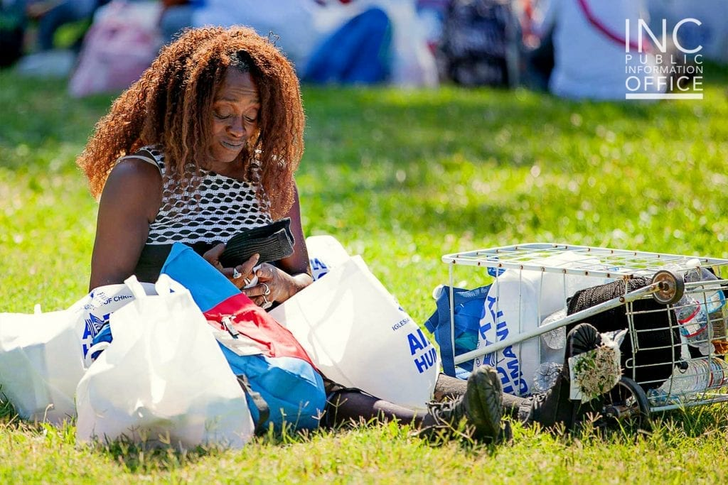 An Oakland resident unpacks the care packages she receives, examining the free new pair of socks she received.