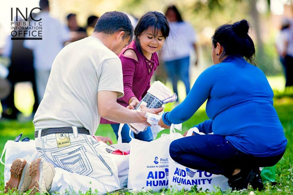 A family of care package recipients unpacks the household goods they've received from the FYM Foundation.