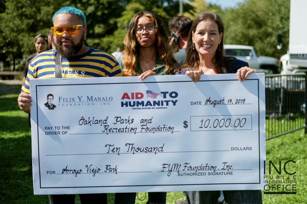 Rodney Williams (left) of the City of Oakland's Parks and Recreation poses with Oakland Mayor Libby Schaaf, with their donation from the FYM Foundation.