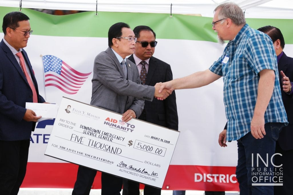 Don Rupp receiving the $5,000 donation from the FYM Foundation on behalf Downtown Emergency Service Center, shaking hands with Brother Glicerio B. Santos Jr., General Auditor of the Iglesia Ni Cristo and representative of the FYM Foundation.
