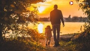 Man walking with a little kid into the sunset.
