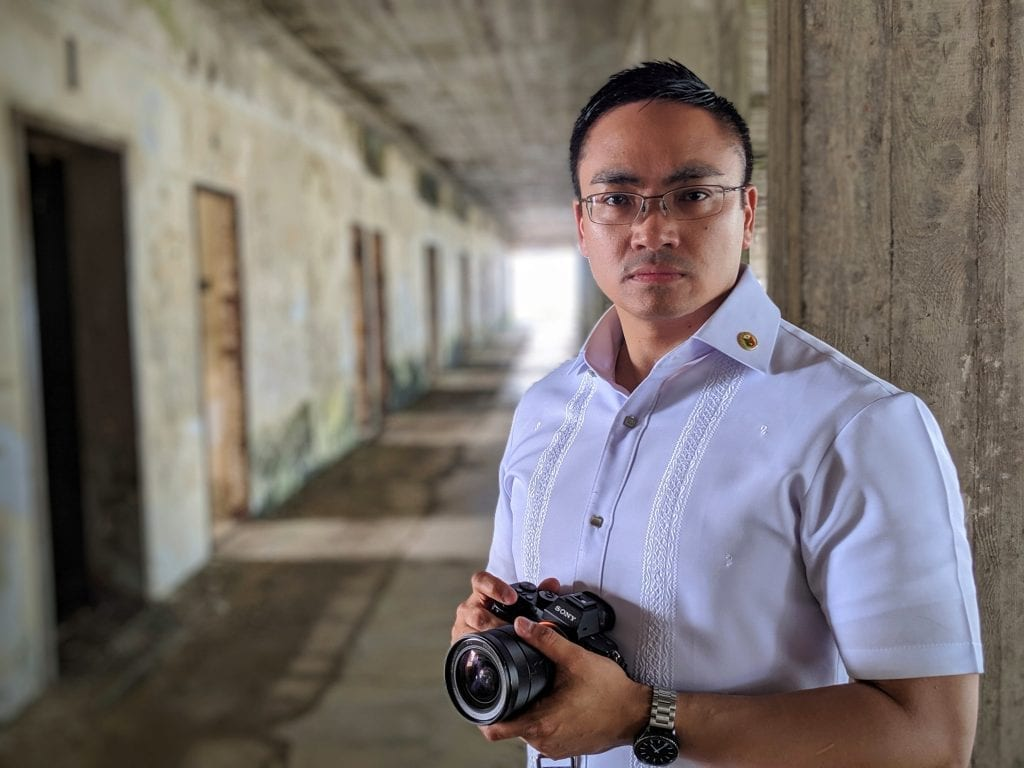 man wearing barong and glasses, holding sony camera