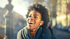 Young woman smiling while listening to podcast
