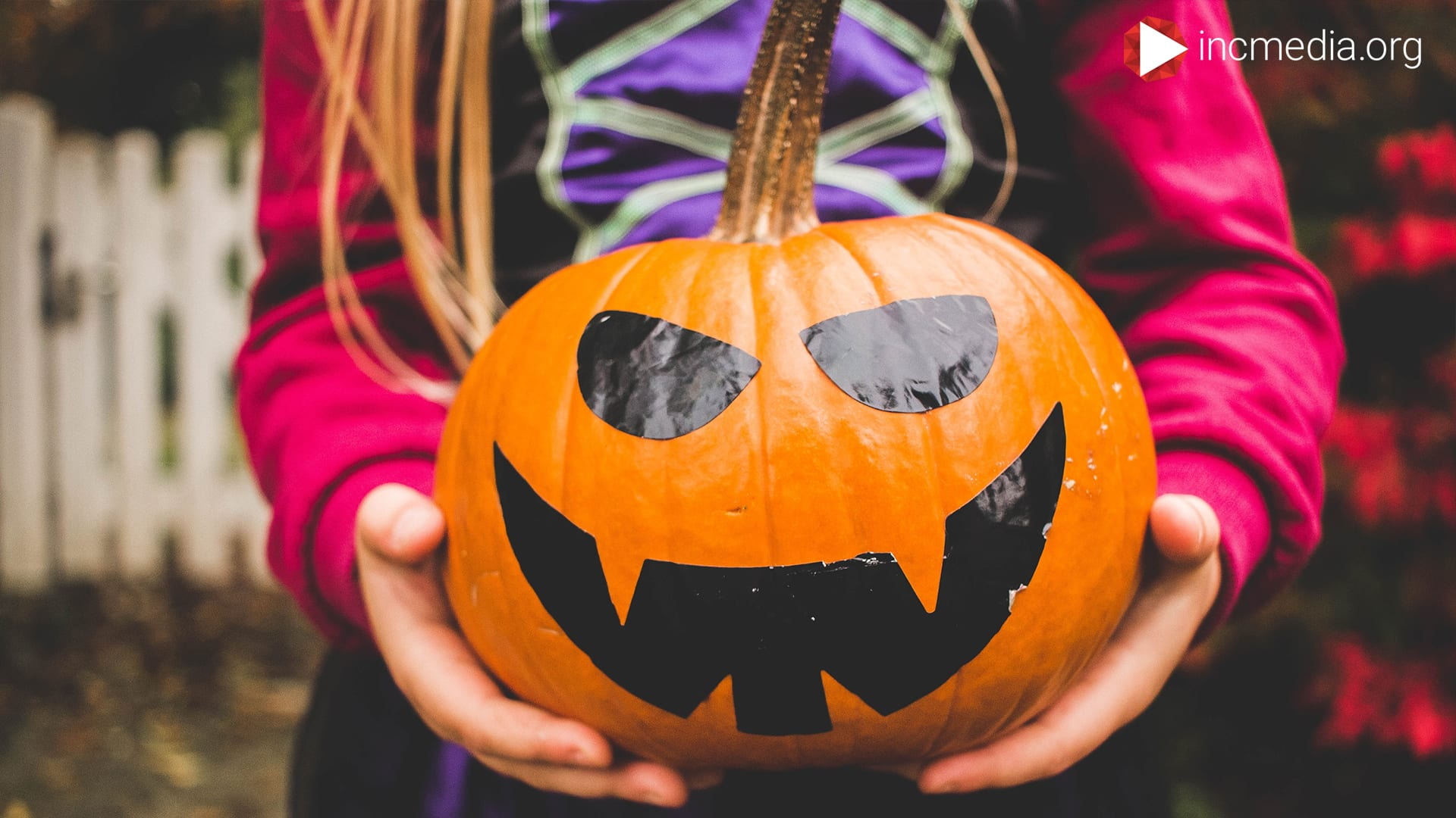 Someone holding a carved pumpkin ready to participate in Halloween.