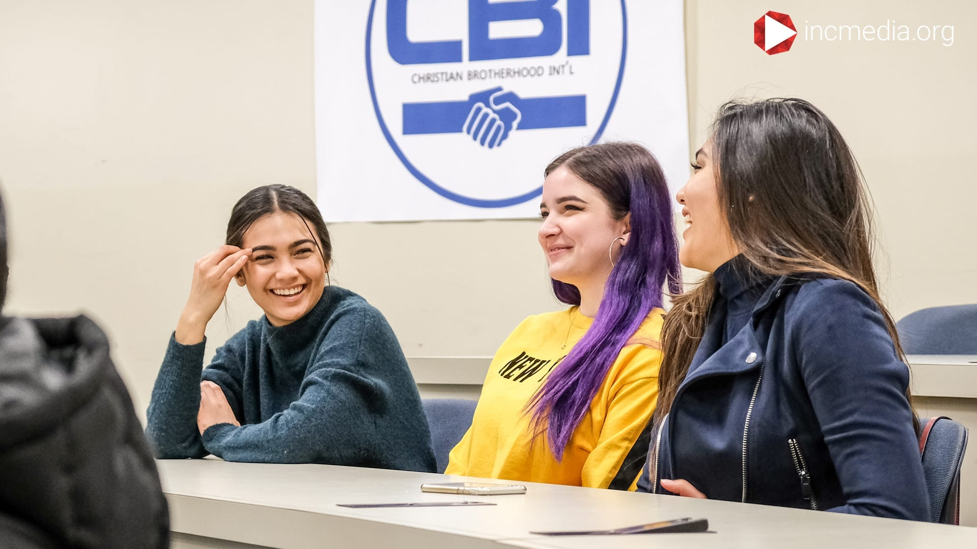 Three college girls smiling and laughing together