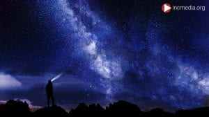 Man looking out into the night sky.