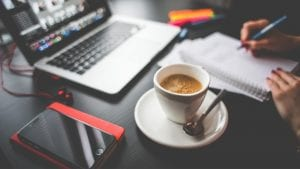 Desk with coffee laptop and notebook
