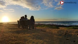 family of four sitting watching the sunset