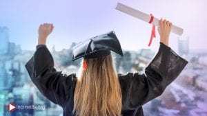 Back of graduate with cap with arms raised
