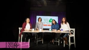 4 women smiling on stage while sitting