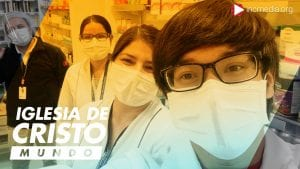 Medium shot of male and female pharmacy workers in masks