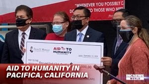 A group of men and women wearing masks stand to pose with a huge check.