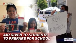 """Two children hold up gift cards for a photo, a woman in a mask holds up a sign that says """"Aid to Students"""" as she waves."""