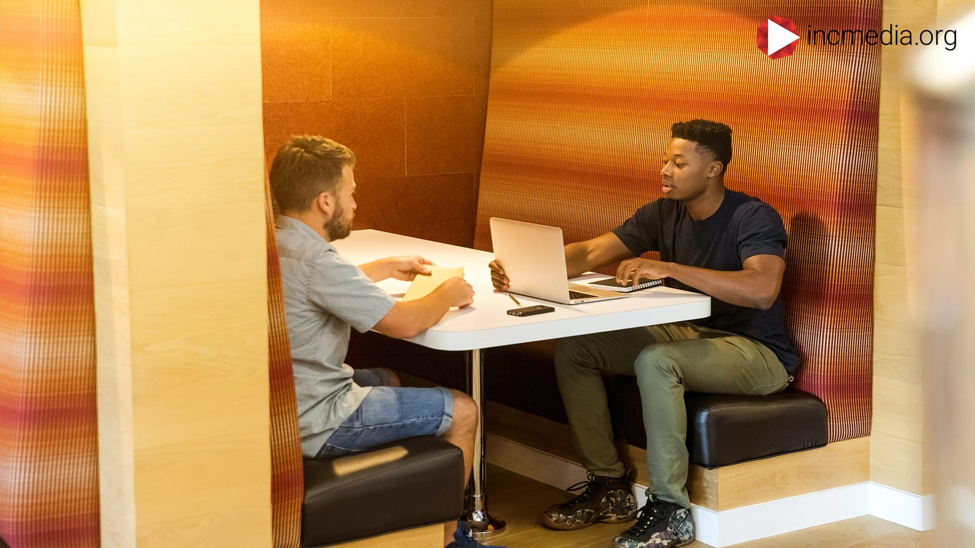 2 men sitting at a table and talking