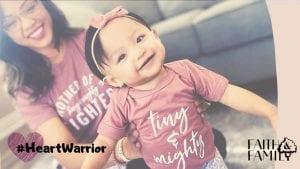 """mother props up her toddler who's wearing a shirt that says """"tiny & mighty"""""""