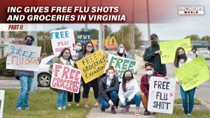 """A group of young adults with masks hold up signs for """"free flu shots"""" and """"free groceries"""""""