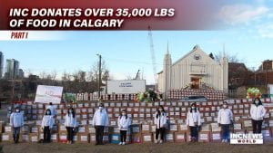 A group of people with masks stand in front of a wall of boxed canned goods with an Iglesia Ni Cristo chapel in the background