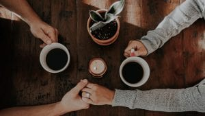 Hands holding over coffee