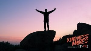 silhouette of man standing on top of rock