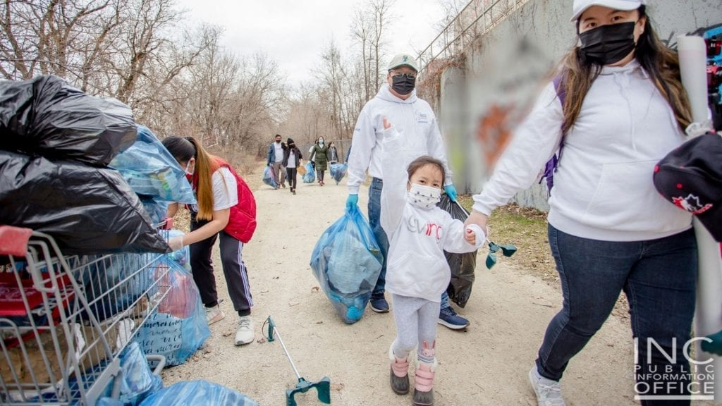 A 4 year old girl waves as she and her parents work with other Iglesia Ni Cristo (INC) or Church Of Christ volunteers during a 2-day Clean-up Drive activity of the Red River riverbank in Winnipeg, Manitoba.
