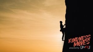 Silhouette of a mountain climber ascending a cliff wall.