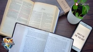 Bibles opened to the book of John on a table with a plant and a phone with the words who is the one true God