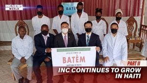A group of people in masks pose for a photo - some men in suits, some wearing white clothing.