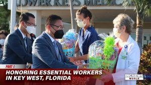 Men with masks hand basket gifts to medical workers