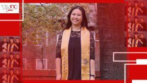 Young woman standing, smiling, wearing graduation sash