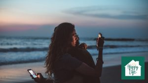A newly married couple hugging on the beach, but both viewing their smartphones.
