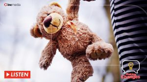 Teddy bear with gold ribbon being held by child