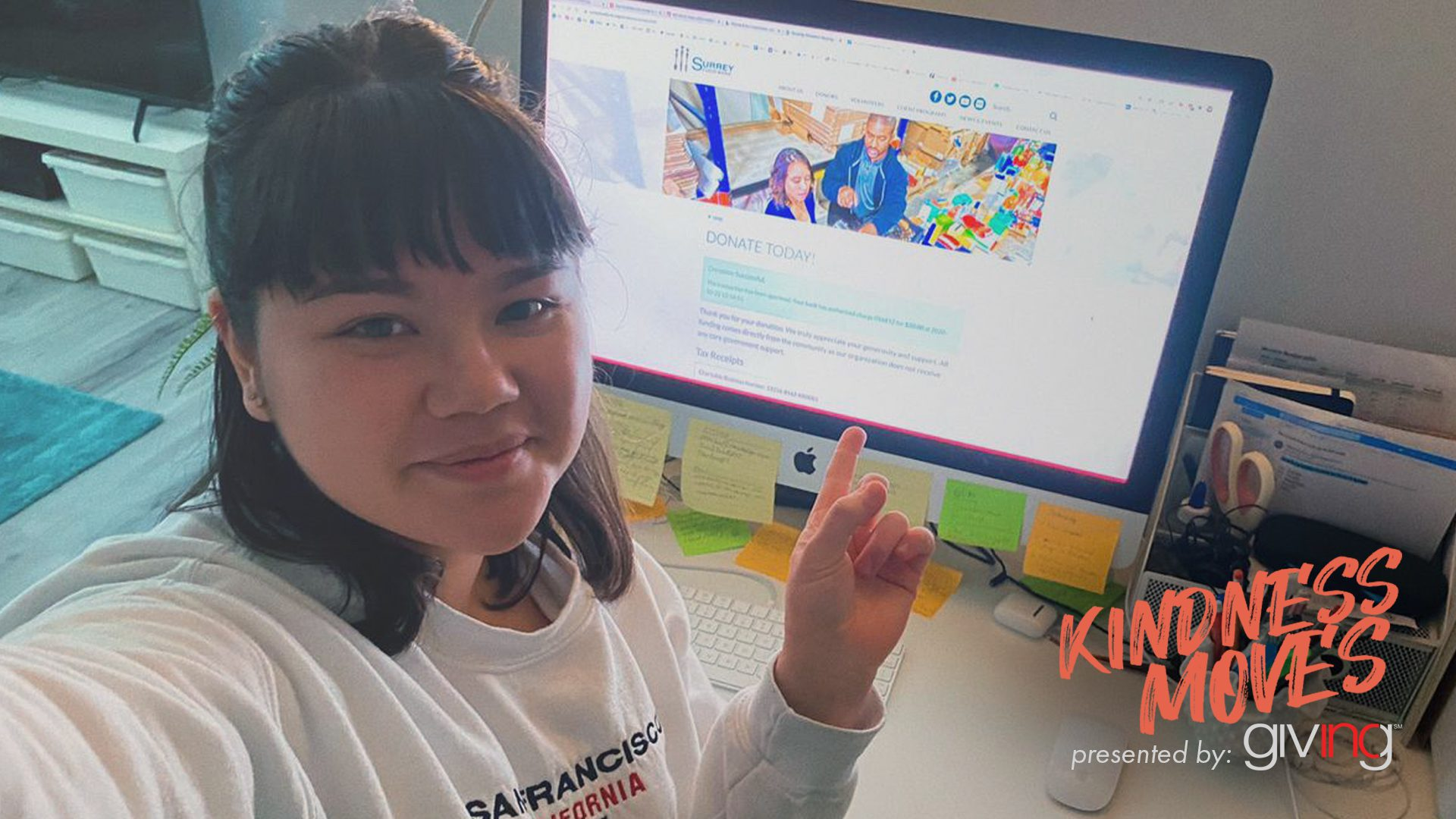 Young woman smiling, sitting in front of computer pointing back to her screen.