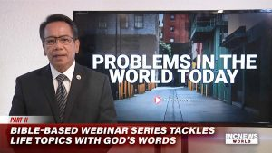 """In the foreground, a man in a suit is speaking, in the background, a graphic with the title """"PROBLEMS IN THE WORLD TODAY"""" is projected in a television screen"""