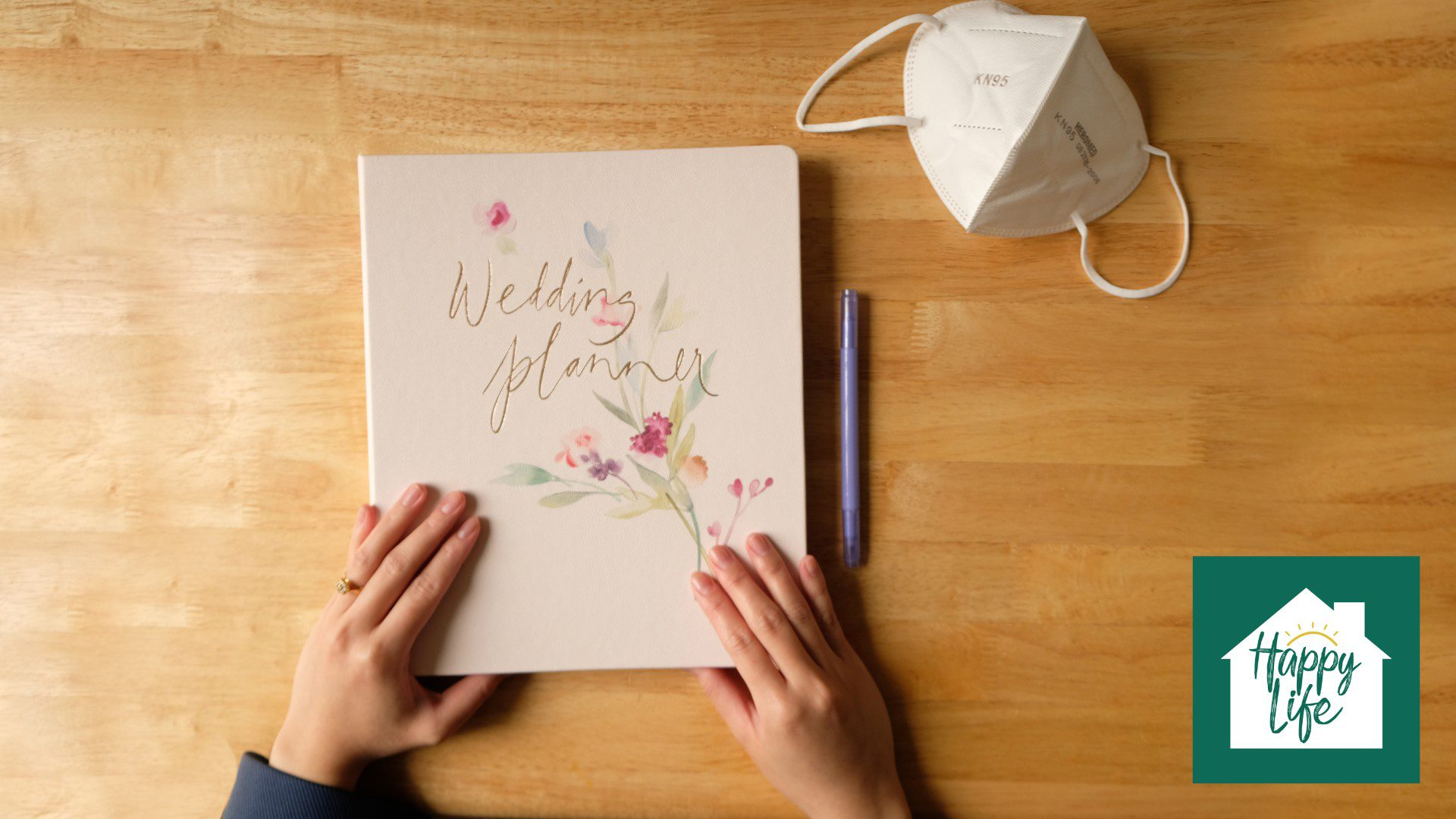 A bride-to-be with both hands on her wedding planner at a table. Her engagement ring is visible and a KN95 mask and pen are on the table beside the planner.