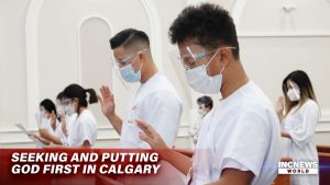 A congregation in white and PPE raise their right hands to take oath
