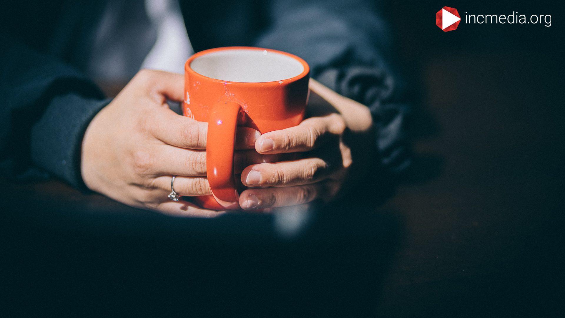 hand holding orange mug