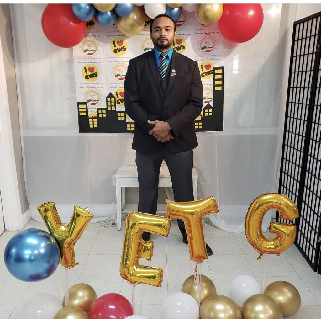 man with balloons spelling YETG