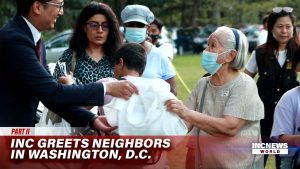 A man in a suit extends his arms to give a care package to an elderly woman with a mask