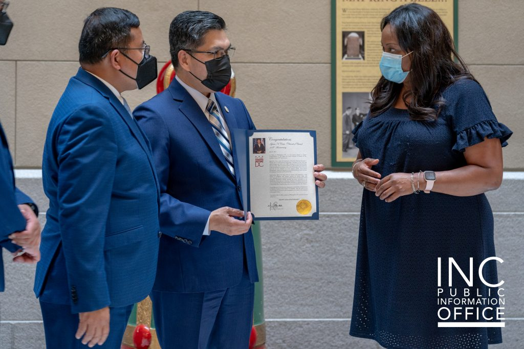 District of Columbia Secretary Kimberly A. Bassett hands over the Mayor's letter of congratulations to INC Minister, Brother Carlitos Medina.
