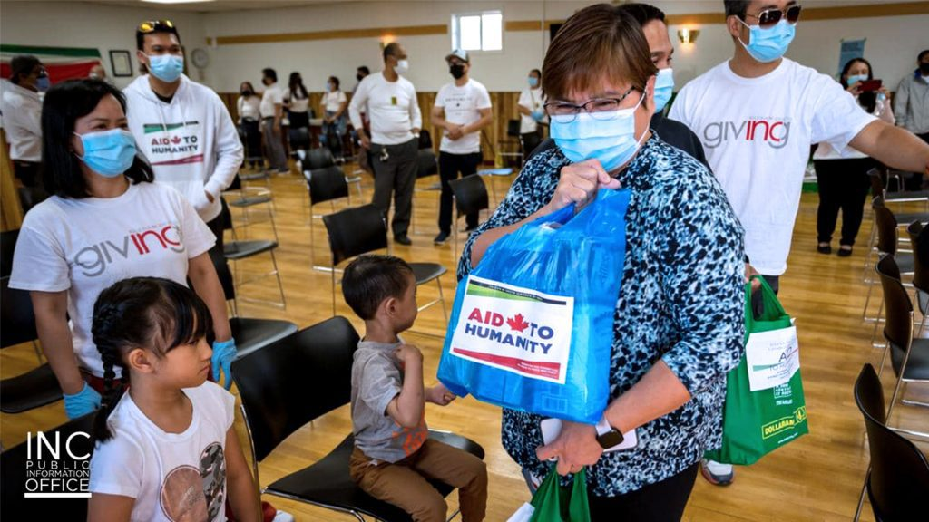 """An excited lady from the town of manning holding a bag of non-perishable food with it labeled """"Aid to Humanity"""""""