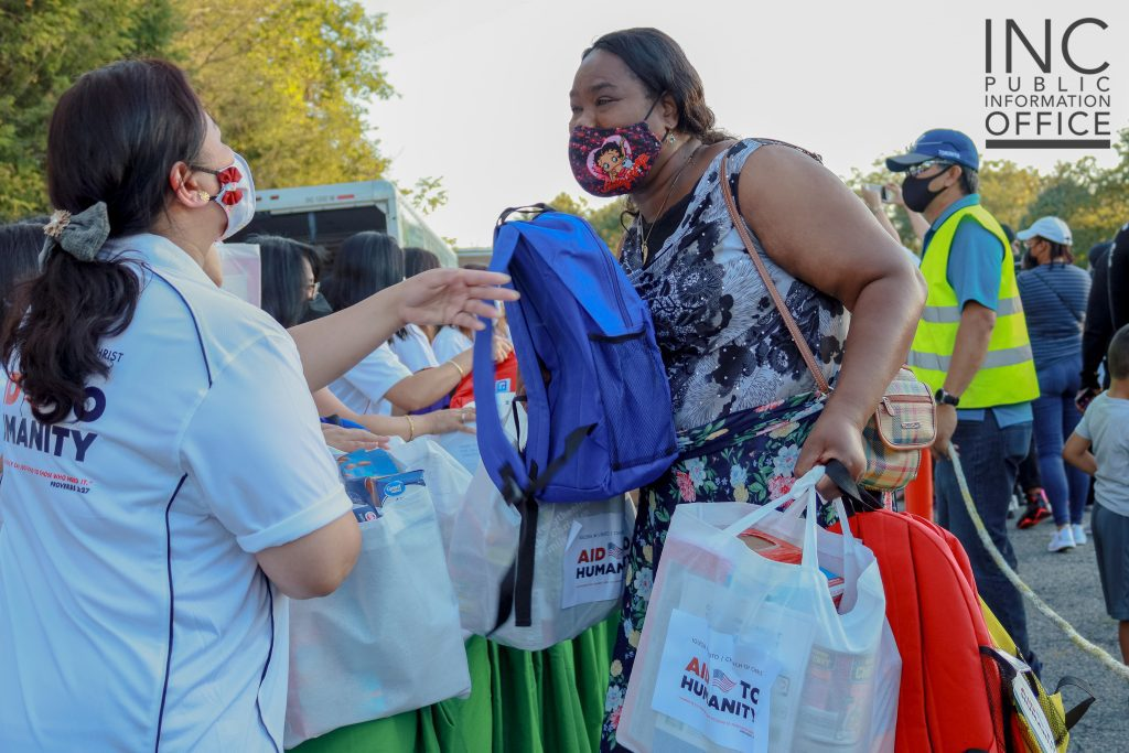 An Aid to Humanity attendee receives a care package of food items and a book bag of school supplies.