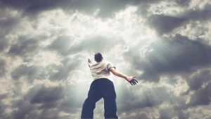 A man reaching up to cloudy skies, with sunlight seeping through the clouds