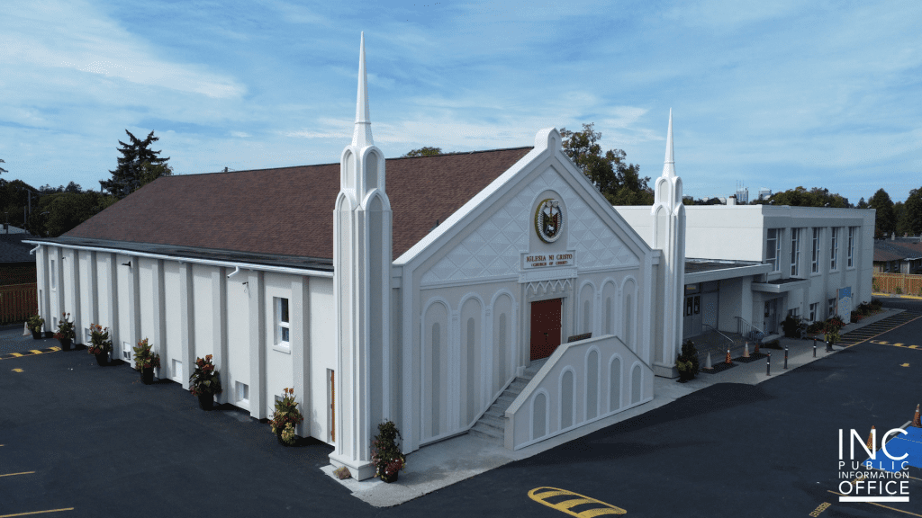 A worship building with steeples, freshly painted and stuccoed in neutral tones with a brown roof.
